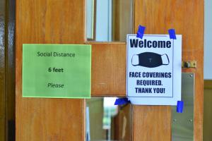 Social Distance and Face Covering Required signs OLA